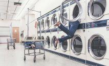 Женщина достает вещи из стиральной машины в городской прачечной. Иллюстративное фото