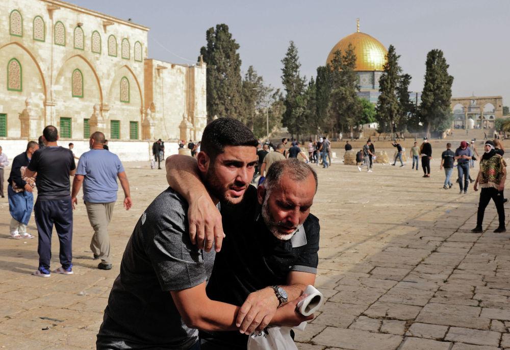 Палестинец помогает раненому протестующему во время столкновений с израильскими силами безопасности в комплексе мечети Аль-Акса в Иерусалиме 10 мая 2021 года, накануне запланированного марша в ознаменование захвата Израилем Иерусалима в ходе Шестидневной войны 1967 года.