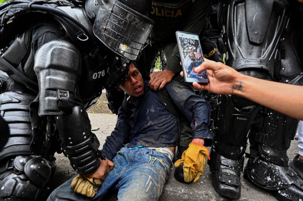 Колумбийские полицейские арестовывают демонстранта во время акции протеста против правительства в Кали (Колумбия). 10 мая 2021 года