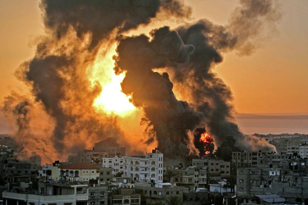 На восходе солнца в Хан-Юнише бушует пожар после израильского авиаудара по целям в южной части сектора Газа. 12 мая 2021 года.  Израильские воздушные налеты в секторе Газа поразили дома высокопоставленных членов боевой группировки ХАМАС, военные заявили в среду, что нападению подверглось и территориальное полицейское управление.