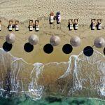Женщина наслаждается солнцем на пляже Плака на эгейском острове Наксос (Греция). 14 мая 2021 года. Греция открыла туристический сезон в пятницу на фоне конкурентной борьбы по Средиземному морю, чтобы заманить отдыхающих, выходящих из изоляции.