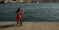Пара танцует у залива Золотой Рог, ведущего к проливу Босфор, разделяющий Европу и Азию, Стамбул