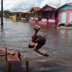 Мальчик прыгает в воду на затопленной улице в Анамане (Бразилия). 14 мая 2021 года