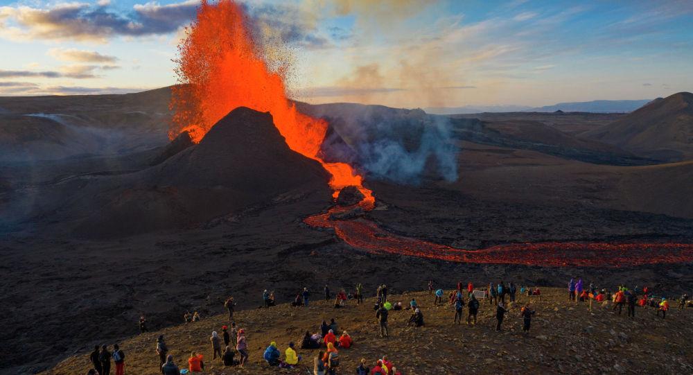 Люди наблюдают как потоки лавы извергаются из вулкана Фаградалсфьяль на полуострове Рейкьянес на юго-западе Исландии