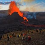 Люди наблюдают как потоки лавы извергаются из вулкана Фаградалсфьяль на полуострове Рейкьянес на юго-западе Исландии. 11 мая 2021 года