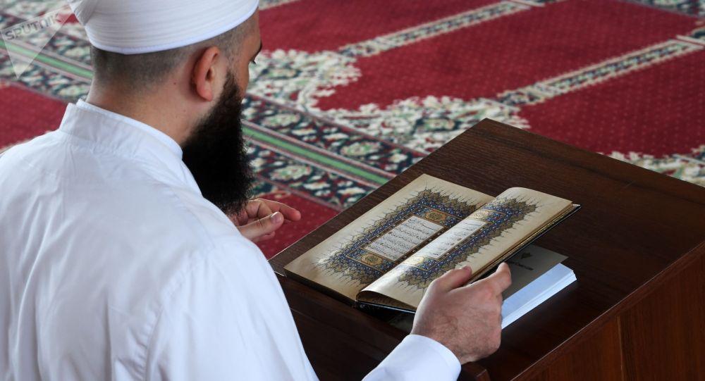 Куран китебин окуп жаткан молдо. Архив