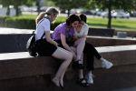Девушки у фонтана в парке смотрят в смартфон. Архивное фото