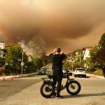 Мужчина фотографирует дым от пожара в государственном парке Топанга на северо-западе от Лос-Анджелеса (США)