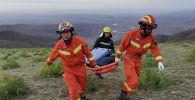 Спасатели несут носилки во время работы на месте, где из-за экстремальных холодов погибли участники ультрамарафонского забега на 100 км в Байине, провинция Ганьсу, Китай. 22 мая 2021 года