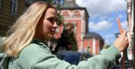 Девушка со смартфоном в руках во время прогулки. Архивное фото