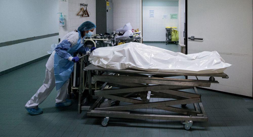 Медик переносит тело пациента умершего от COVID-19. Архивное фото