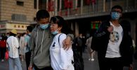 Люди прибывают на вокзал в Пекине