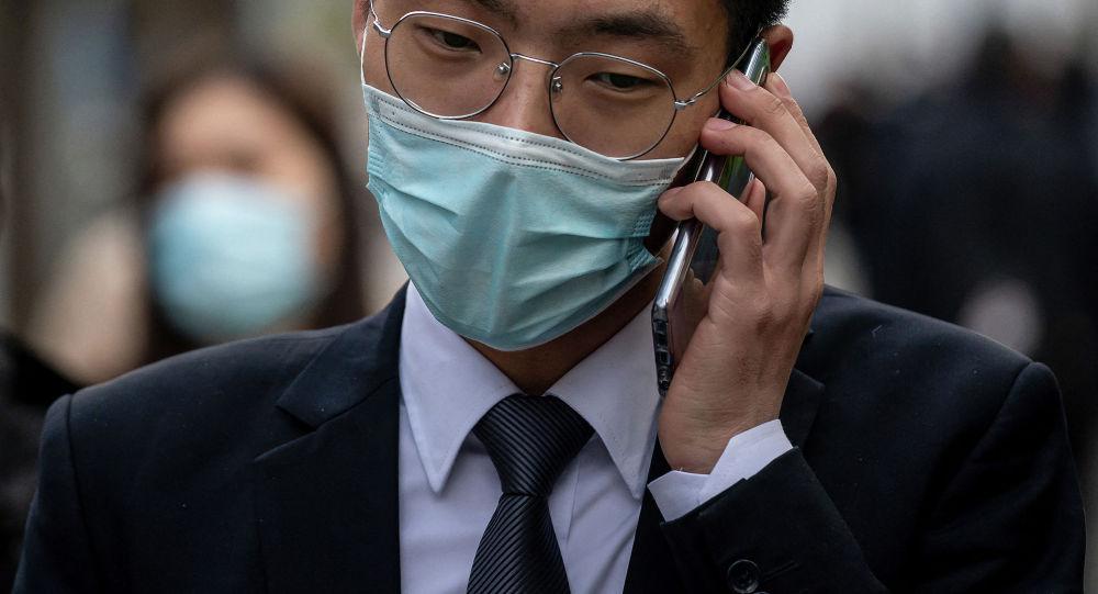 Мужчина в маске разговаривает по телефону на улице. Архивное фото