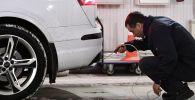 Технический эксперт проводит осмотр автомобиля на СТО. Архивное фото
