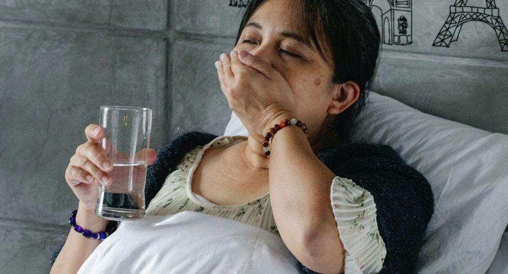 Женщина принимает лекарство от кашля. Иллюстративное фото