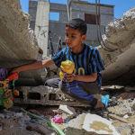 Палестинский мальчик достает игрушки из обломков своего дома в Хан-Юнисе (сектор Газа), который был разрушен израильскими авиаударами. 26 мая 2021 года