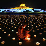 Буддийский монах зажигает свечи в храме Ват Дхаммакая в Бангкоке, Таиланд. 26 мая 2021 года