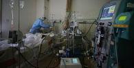 Медициналык кызматкер ооруканадаа COVID-19 менен ооруган адамды кабыл алып жатат. Архив