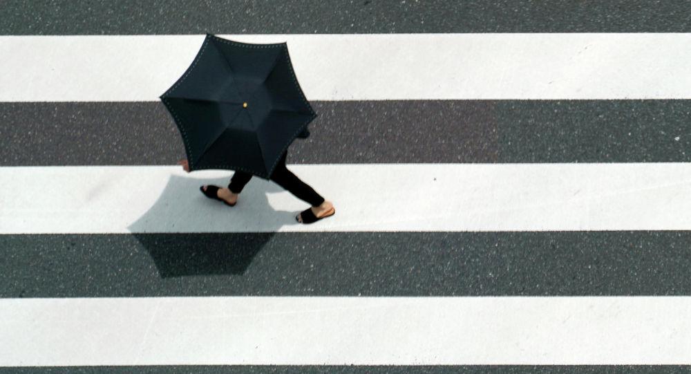 Девушка с зонтом переходит дорогу. Архивное фото