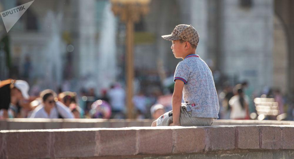 Мальчик сидит у фонтана на площади Ала-Тоо в Бишкеке. Архивное фото