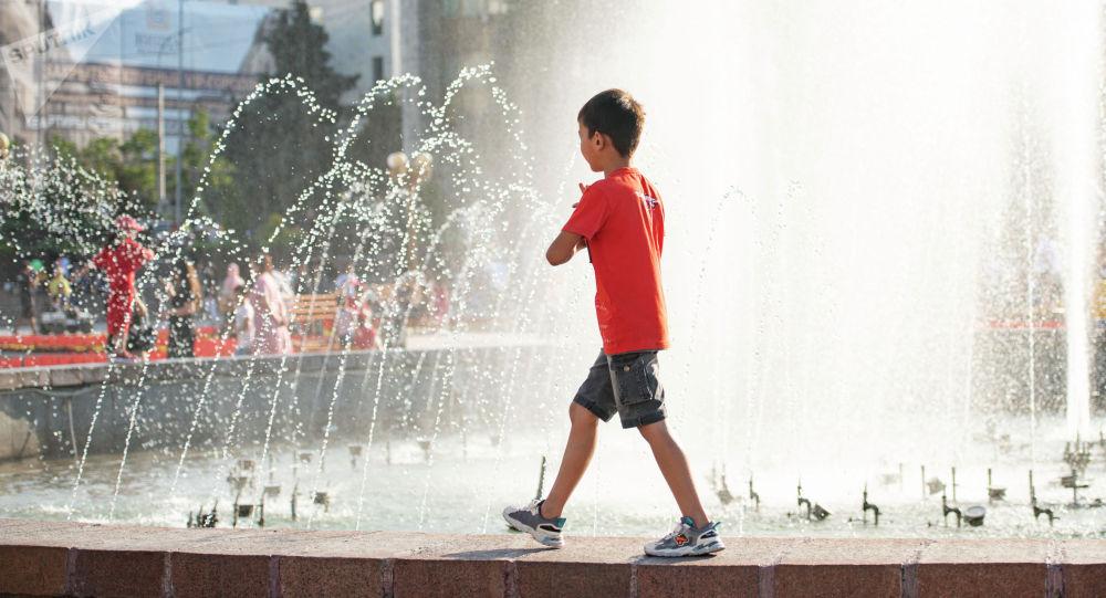 Мальчик идет вдоль фонтана на площади Ала-Тоо в Бишкеке. Архивное фото