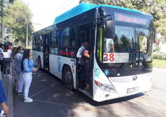 Заполненный пассажирами автобус на остановке напротив здания Юридической академии в Бишкеке