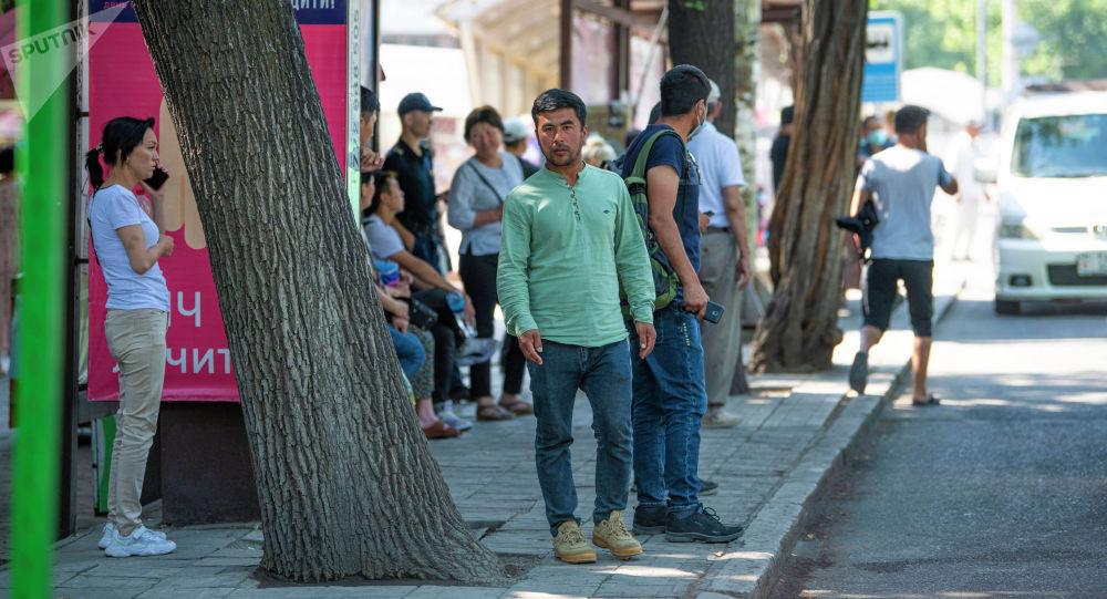 Жители Бишкека на одной из остановок Бишкека ждут общественный транспорт