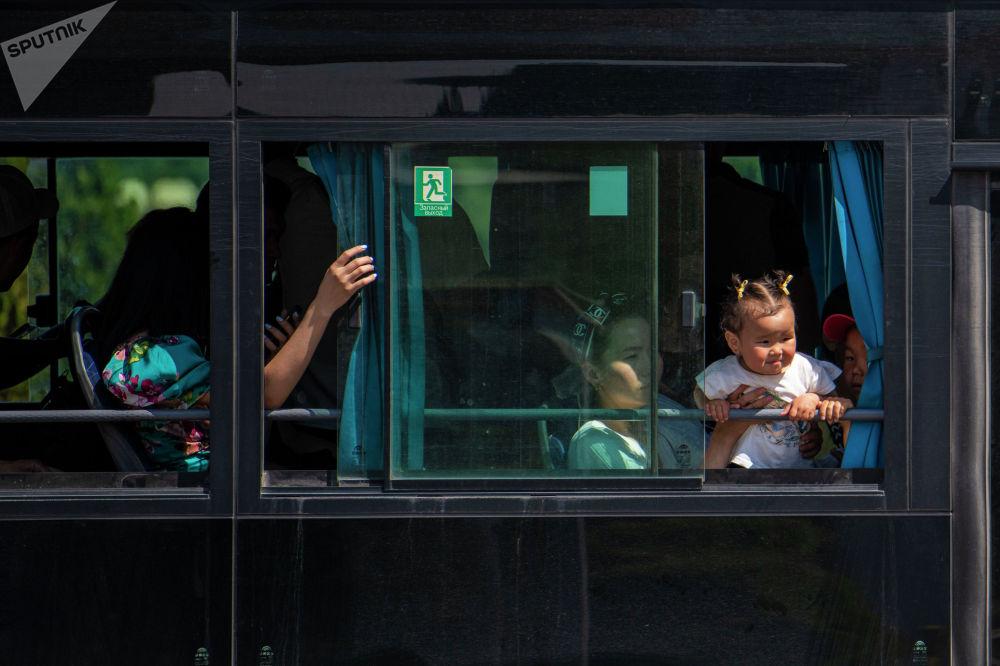 Ребенок выглядывает из окна автобуса после того, как водители маршрутного такси устроили забастовку в Бишкеке