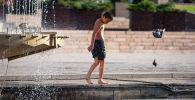 Мальчик купается в фонтане на площади Ала-Тоо в Бишкеке