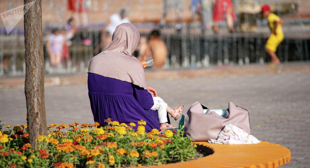 Женщина с ребенком сидит на скамейке на площади Ала-Тоо в международный день защиты детей в Бишкеке. 1 июня 2021 года