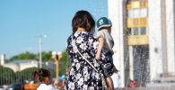 Женщина с детьми у фонтана на площади Ала-Тоо в Бишкеке