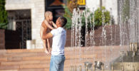 Мужчина купает ребенка в фонтане на площади Ала-Тоо в Бишкеке. Архивное фото