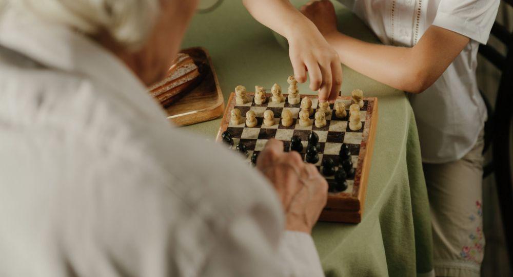 Карыя киши небереси менен шахмат ойноп жатат. Иллюстративдик сүрөт