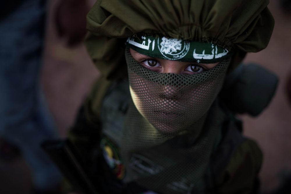 ХАМАС менен Израилдин ортосундагы 11 күнкү атышуудан кийин тартылган сүрөт. Оюнчук курал кармаган бала