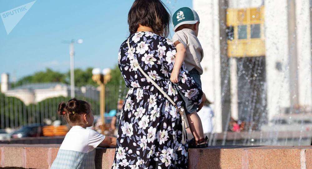 Женщина с ребенком у фонтана на площади Ала-Тоо. Архивное фото