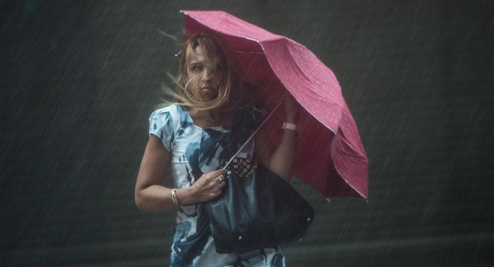Женщина с зонтиком под сильным дождем и ветром. Архивное фото