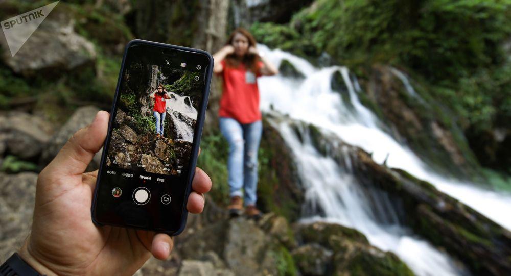 Туристы фотографируются у водопада. Архивное фото