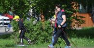 Женщины занимаются скандинавской ходьбой в парке. Архивное фото