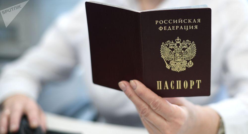 Сотрудник держит в руках паспорт РФ. Архивное фото