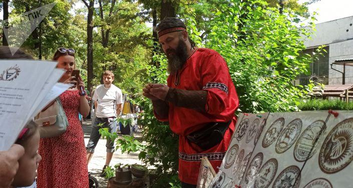 Мужчина в русском национальном костюме за прилавком сувенирной продукции на масштабном фестивале, посвященном Дню России, который прошел возле Русского драмтеатра в центре Бишкека