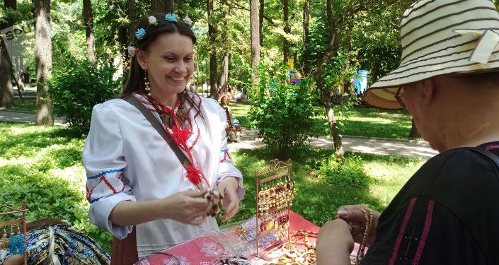 Женщина в русском национальном костюме за прилавком сувенирной продукции на масштабном фестивале, посвященном Дню России, который прошел возле Русского драмтеатра в центре Бишкека