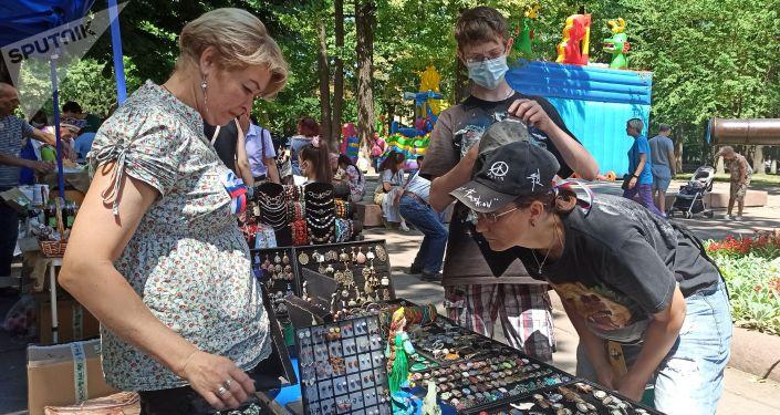 Женщина за прилавком сувенирной продукции на масштабном фестивале, посвященном Дню России, который прошел возле Русского драмтеатра в центре Бишкека