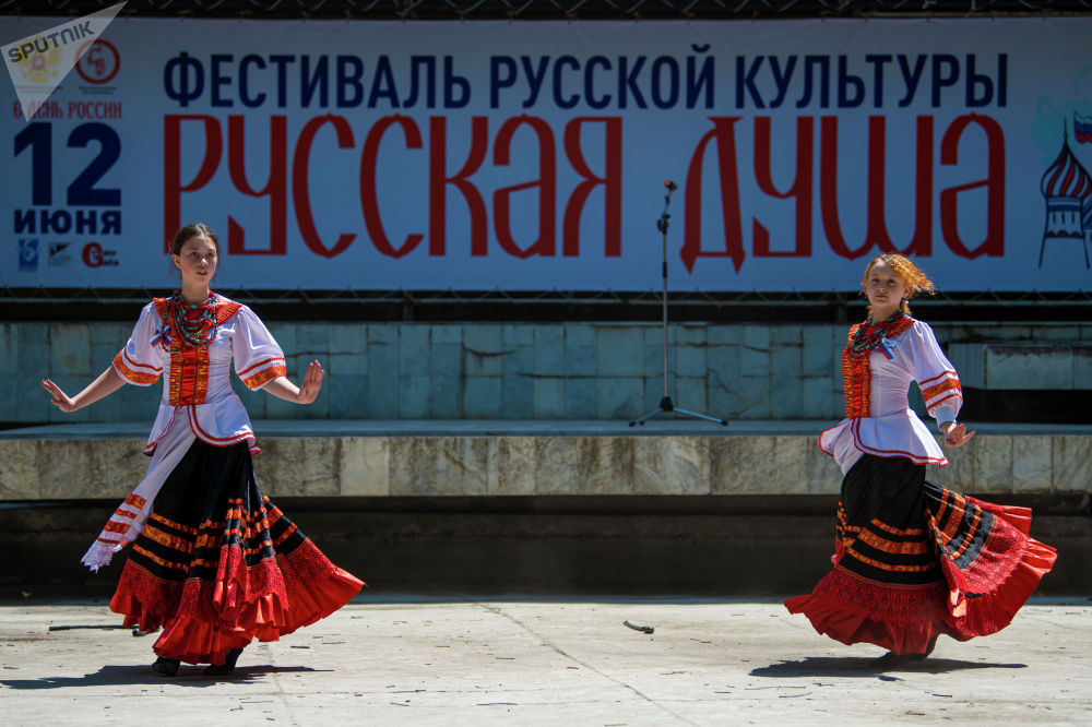 Женский ансамбль выступает на масштабном фестивале, посвященном Дню России, который прошел возле Русского драмтеатра в центре Бишкека