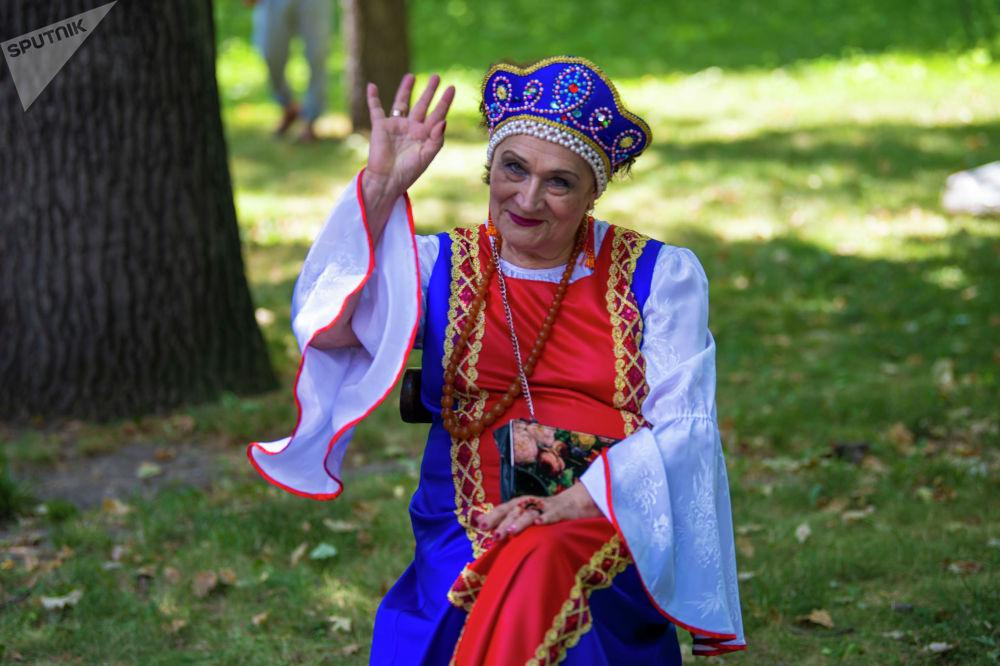 Женщина в русском национальном костюме на масштабном фестивале, посвященном Дню России, который прошел возле Русского драмтеатра в центре Бишкека