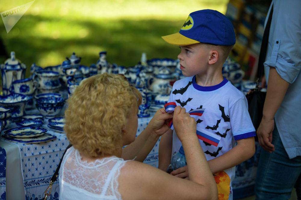 Женщина с ребенком на масштабном фестивале, посвященном Дню России, который прошел возле Русского драмтеатра в центре Бишкека