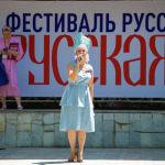 Девушка во время выступления на масштабном фестивале, посвященному Дню России, который прошел возле Русского драмтеатра в центре Бишкека