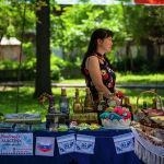 Девушка за прилавком сувенирной продукции на масштабном фестивале, посвященном Дню России, который прошел возле Русского драмтеатра в центре Бишкека