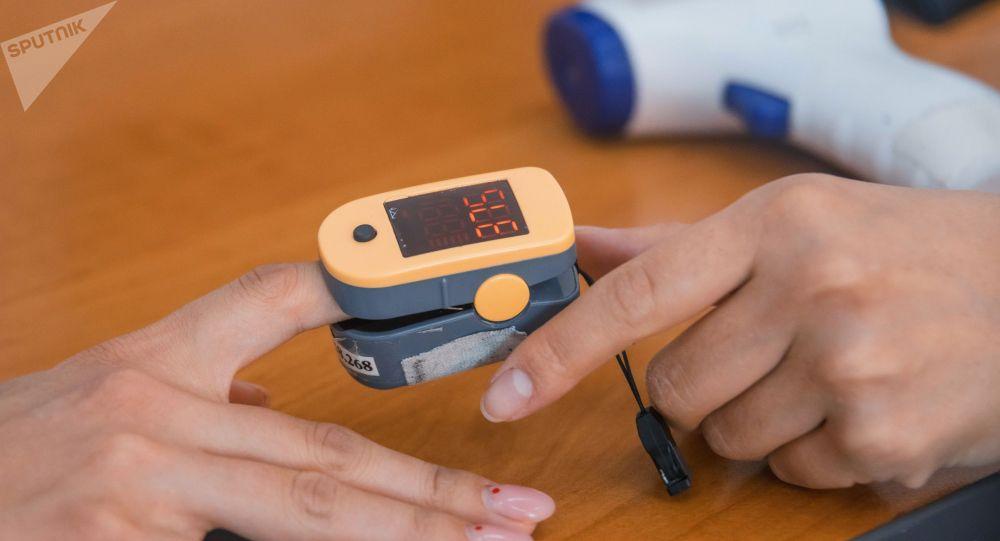 Медицинский сотрудник измеряет температуру тела и уровень кислорода в крови у пациента. Архивное фото