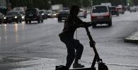Девушка едет на электросамокате во время дождя. Архивное фото