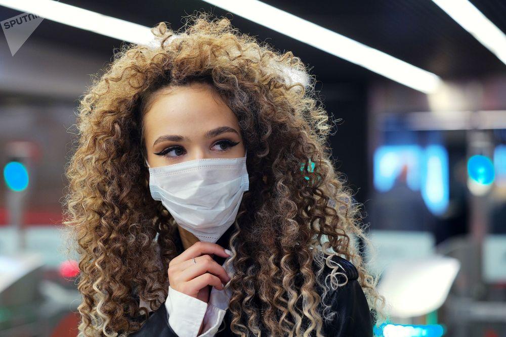 Девушка в маске на станции Полежаевская московского метрополитена.